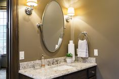 Master bathroom with double vanity. Oval mirrors flanked by sconces. Fluff Interior Design - Decorating for REAL life! Omaha, NE.