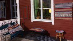 Inred terass eller balkong med kuddar och väggförvaring av återanvänd trasmatta.