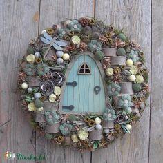 A széles- lapos formára készített alapot textillel dolgoztam el, majd közepébe rögzítettem a pici fa ajtót. A mentára színezett ajtó köré először pici, félbehasított fa rönköket és saját készítésű ezüstös fényű szatén rózsákat ragasztottam, majd zöldre színezett mákgubókkal, olaj színű eukaliptusztermésekkel és szürkés valamint natúr szárított növényi részekkel borítottam az alapot. A termések közötti részeket, ezüstös zuzmóval és szárított mohával töltöttem ki. Világossárga bogyókkal…