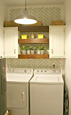 love the wood shelves between the cabinets in this laundry room