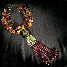 This piece is the second half of a two-part Parrot buckle I found at a Vintage show. Its plastic, with a lovely shine and suggested Carmen Miranda to me, wearing it belted around her waist with one of her swirly, gauzy, Mexican skirts. I made the first half of the Parrot buckle necklace with yellow jade. Here I have chosen to use giant bronze Keishi pearls and a long baroque pearl tassel. The Keishi pearls are the apex of the freshwater pearl growers art, an exaggerated size of about an…