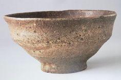 028 柿の蔕茶碗 銘「毘沙門」 畠山記念館 次に紹介するのは、井戸茶碗同様に大変侘びた見た目を持っている柿の蔕茶碗です。他の茶碗との判別は至極簡単で、独特の形状をした胴、ゴツゴツした肌、柿の蔕のごとき渋茶色の特徴があればそれは柿の蔕茶碗でしょう。上の「毘沙門」は柿の蔕の代表作で、国の重要文化財に指定されています。井戸とは違って貫入・カイラギはありませんが、井戸とはまた違った味わい深い侘びが宿っています。少し伊羅保茶碗にも似ていますがそのところはあとで指摘したいと思います。