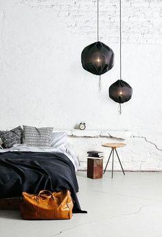 Dark bedding, rough, textured white walls.