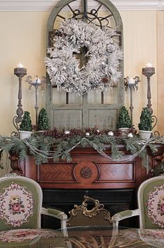 Love the big vintage window, tall candlesticks, & little trees in pots on the mantel.