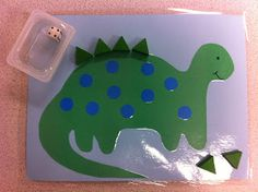 "Math Mats: Reinforce lesson on ""How many more/fewer?"" Players roll the die and placed that many spikes (green blocks) on the dinosaur. They then determined how many more were needed to make five/ten."
