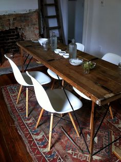 dining area ~ kilim; rustic & warm wood table + Eames-style shell chairs.