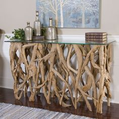 Uttermost Teak Wood Console Table - The Uttermost Teak Wood Console Table from artist Matthew Williams is a in intricate sculpture of reclaimed teak wood beneath a sheet of clear glass p...