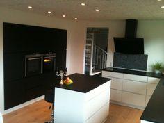 Mit dejlige køkken i sort/hvid. Den sorte skabsvæg er i sort eg og fungerer super godt. Bag lågerne gemmer der sig et stort lækkert køleskab, microovn og masser af opbevaring. Jeg er vild med kontrasten mellem det sort hvide, de rene linier med grebsløse skuffer og alligevel plads til lidt rod og hygge :-)