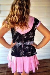 Back view of girls pirate costume, black bodice over pink dress. Zips up the back with zebra ribbon going around her waist.