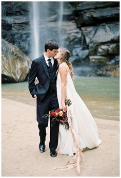 Bride and groom kissing at Toccoa Falls in Georgia. Bouquet by Lauren Emerson Events & Design. Dress by Carol Hannah. Image by Melanie Gabrielle.