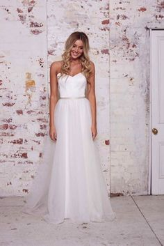 An adorable A-line wedding dress made with tulle and a thin silver belt from Karen Willis Holmes' The Wild Hearts Collection