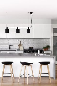 A light gray subway tile backsplash is a fresh departure from white, especially when balanced by a coordinating gray counter and black décor accents. Scandinavian Modern, Scandinavian Kitchen, Kitchen Tops, New Kitchen, Kitchen Decor, Kitchen Ideas, Loft Kitchen, Condo Kitchen, Kitchen Inspiration
