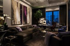 The large expanse of wall above the sofa in this contemporary urban living room makes the perfect landing place for a pair of paintings. The color palette in the art is picked up in the room with the addition of purple accent pillows, accessories and a chair.