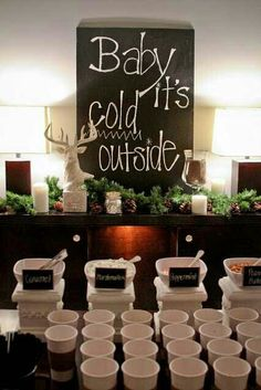 Hot chocolate station for a winter wedding. 'Baby it's cold outside' sign.
