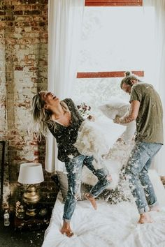 This Couple's Pillow Fight Photo Shoot is Fun, Flirty, and Full of Feathers Adorable engagement photos that don't even require leaving the bedroom