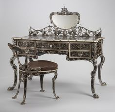 RISD Museum: Gorham Manufacturing Company, manufacturer, American, 1831-; William Christmas Codman, designer; Joseph Edward Straker, silversmith; Franz Ziegler, modeler; Potter and Company, cabinetmaker. Lady's writing table and chair, 1903. Ebony, mahogany, boxwood, redwood, thuya wood, ivory, mother-of-pearl, silver, mirrored glass, and gilded tooled leather. 127 x 127 x 71.1 cm (50 x 50 x 28 inches). Gift of Mr. and Mrs. Frederick B. Thurber 58.095
