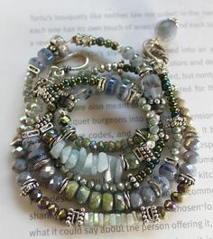A new stunning wrap bracelet with vivid stones of beautiful blues and greens! ~5 strands featuring: strand of soft gold green crystal to a deeper soft blue crystal. to ab treated deep green faceted crystal to stacked square silver beads center stacks of Ab mystic treated multifaceted