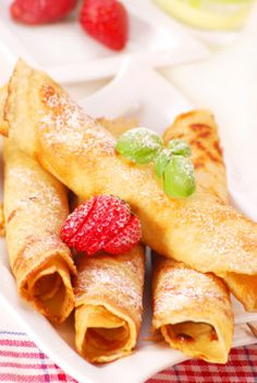 Rolled pancakes with powder sugar and strawberry