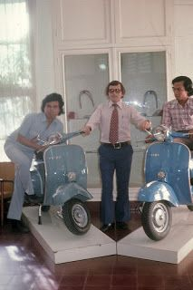 Three men posing with two Vespa scooters in their factory owned by PT Dan Motor Indonesia, about 1970.
