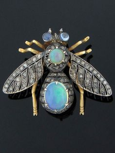 Antique 9K gold jeweled bee pin, circa 1910. This bee pin is expertly hand made of 9 karat white and yellow gold. It has a prong set oval cabochon opal on the body at approximately 1.59 carats and a prong set round cabochon opal on the head at approximately .50 carat. Both opals are of fine quality. The bee has two bezel set round cabochon light blue sapphire eyes at approximately .18 carat total weight that are of good quality.