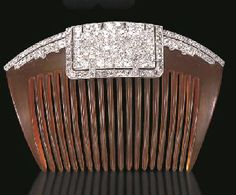 N ELEGANT ART DECO TORTOISE SHELL AND DIAMOND HAIR COMB  The arched tortoise shell comb decorated with an old mine and old European-cut diamond plaque, with rose-cut diamond trim, extending similarly-set diamond lines, mounted in platinum, circa 1925 .