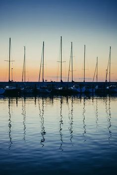 A series of sailboats docked at the harbor reflects over the water creating a beautiful rhythm #InnerLightLeaks #reflection #sunset #boat #picture #photography