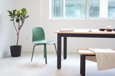 Picture of our Stir Parsons table with ebonized base and oiled white ash top. Shown with Muuto chair in green and Stir Bench.