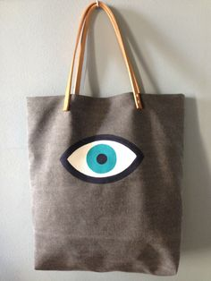 Sac cabas en pur lin gris, motif charm eye peint à la main. Leather Purse Diy, Diy Purse, Leather Purses, Tod Bag, Felt Flower Pillow, Painted Canvas Bags, Greek Evil Eye, Evil Eye Jewelry, Hamsa Hand