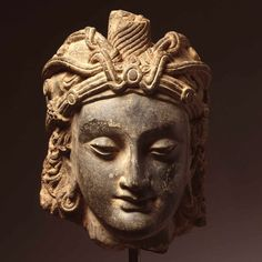 A grey schist stone head of a young man, 3rd century AD, Gandhara