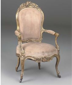 A VICTORIAN GILTWOOD ARMCHAIR  MID-19TH CENTURY  Carved throughout with scrolling foliage and rockwork with a padded cartouche shaped back, open arms with scrolled terminals and a bowed seat on channelled cabriole legs.