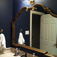 Boys bathroom painted Farrow and Ball Blue Black. Hollywood Regency style gold mirror. Great vintage horse head hook. Visual Comfort Vendome sconce.