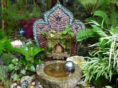 A simple fountain spills in to a carved stone bowl from China, surrounded by lush plantings