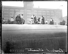 Rescuers and survivors atop the hull of the overturned Eastland steamer in the Chicago River on July 24, 1915. Photograph from the Chicago Daily News.