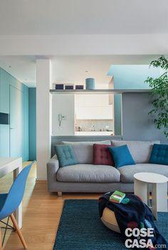 zona giorno del sottotetto su due livelli, divano grigio, cuscini trapuntati, tavolino bianco, pouf, tappeto, mobile su disegno con porta rasomuro integrata, pilastro, parete divisoria