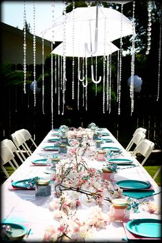 Umbrellas showering down crystals for baby shower decor.