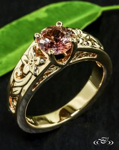 Golden Floral & Peach Sapphire Engagement RingFlowers cast in yellow gold bloom around a trellis set peach sapphire atop this unique engagement ring. #Ido #GreenLakeMade #EngagementRing