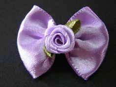 Laço confeccionado em fita de cetim lilás com enfeite de florzinha.                 Prazo para confecção 03 dias úteis                 Preço por unidade.                 Medida: 4,0 cm x 3,0 cm R$ 0,60