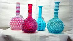 In the 19th century, barbers filled their own bottles with hair tonic and oil, shampoo and rosewater. The bottles came in distinctive colors/shapes so the barber could identify what was in each one of them.   These Fenton 19th century barber bottles with coin dot & hobnail come in various colors! We love the character and history they bring to a home. #vintage #antique