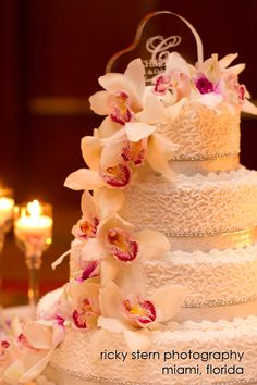 Round Four Tier Wedding Cake With Fresh Cascading Orchids And A Heart Shaped Glass Topper