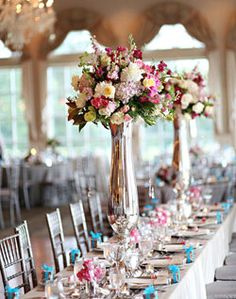 I like the long tables with tall centerpieces alternating with several smaller ones.