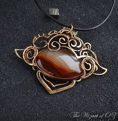 Wire wrapped bronze pendant Mongolia with Carnelian cabochon. Like the unexpected fire of a sunset, or the first flash of autumn brilliance, Carnelian captivates attention with its distinctivecolor. This delightful design features an oval-shaped Carnelian in an elaborate wire frame.