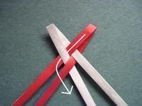 ここで使っているテープは、 幅:5㎜ 長さ:赤27cm、白30㎝、青19cmくらいです。  幅の太さでテープの長さがかわります。 テープの厚みや折り方によってもかわりますから、余裕をもって用意してくださいね。  中央で軽く2つ折りにしたテープを交互に重ねて組み合わせます。 テープをしっかり組みあわせたら、左端の赤テープを白テープにそうように谷折りします。 *青テープ2本も同じように折っていきます。