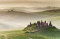 In this beautiful sunrise capture, we see an amazing farmhouse located near Pienza and San Quirico d'Orcia in Tuscany, Italy. The morning fog over the rolling hills makes for an idyllic scene.
