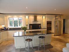 Shaker style kitchen in cream painted solid wood doors, granite work top, space for range, wine racks, American fridge freezer and larder cupboard.