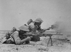 British Bren gunner with a machine gun covers digging a trench comrade during the Battle of El Alamein.