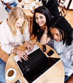 Three young people gather round open laptop in coffee shop Royalty Free Stock Photo