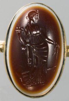 Gemme: Stehende Fortuna. Römisch, Republikanisch 3. Viertel 1. Jh. v. Chr. Sardonyx, mehrschichtig, dunkelbraune, undurchsichtig weiße, geblich durchscheinende Schicht. In moderner vergoldeter Fassung als Ring.