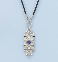 AN ART DECO DIAMOND AND GEM-SET PENDANT/BROOCH   The diamond-set shaped rectangular panel with central sapphire and diamond collets suspended from a diamond hoop to the black rope necklace, circa 1920, panel 5.3 cm. long, necklace 51.8 cm. long