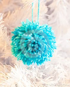 A closeup of a bright woolly handmade Christmas decoration on the branch of a white xmas tree.