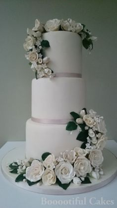 It's all in the detail - a little bit of ribbon goes a long way! Here it gives a hint at the colour scheme but keeps the neutral tone of the design complimenting the flowers too! Wedding cake design by Booootiful Cakes: www.booootifulcakes.co.uk
